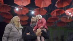 Young family walking under the city umbrella decoration
