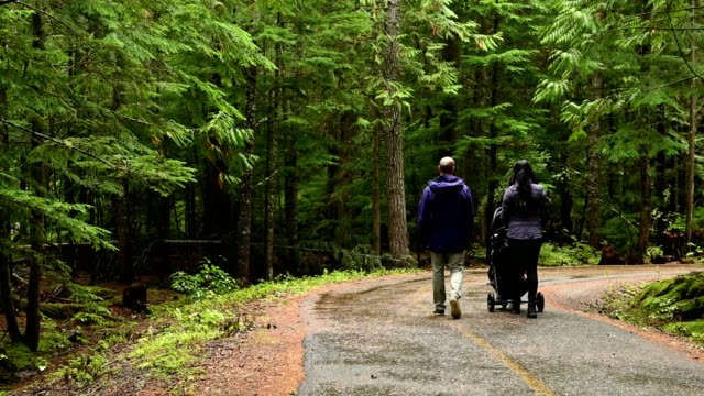 young family with a stroller in the rain - young family stock videos & royalty-free footage