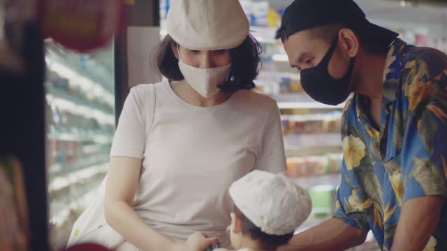 フェイスマスクで子供の女の子と若い家族はスーパーマーケットで買い物 - 両親点の映像素材/bロール