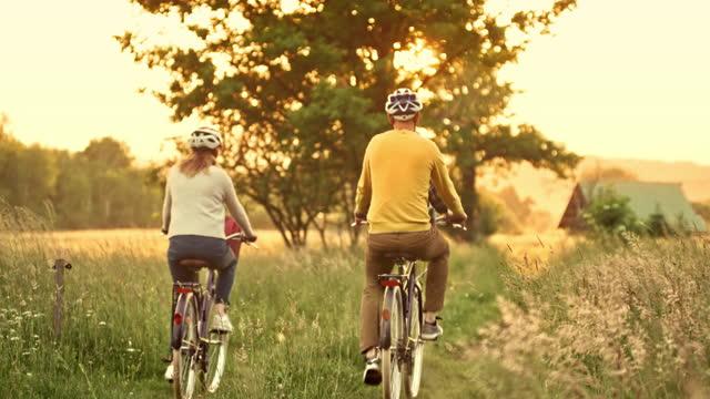 vidéos et rushes de ld jeune famille avec l'enfant dans le siège d'enfant conduisant leurs bicyclettes dans la campagne au coucher du soleil - monter sur un moyen de transport