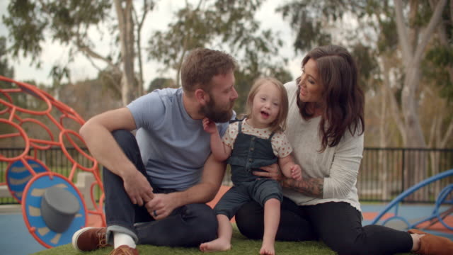 young family with down syndrome daughter sitting together in the park - sindrome di down video stock e b–roll