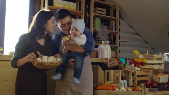 vídeos y material grabado en eventos de stock de young family with little child standing at their own shop - tienda de fruta y verdura