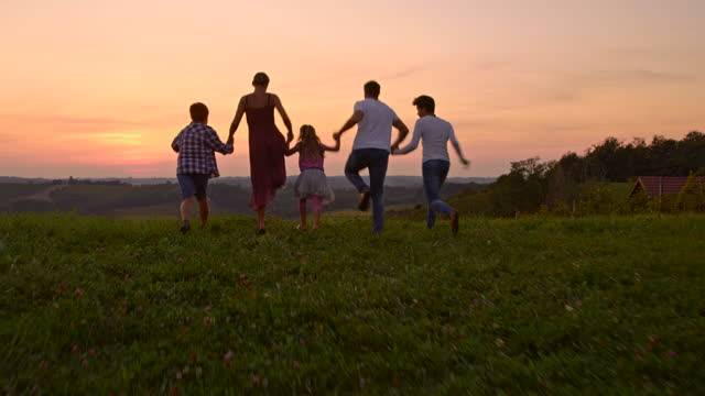 slo mo young family with three children having fun jumping up in the air at sunset - family with three children stock videos & royalty-free footage
