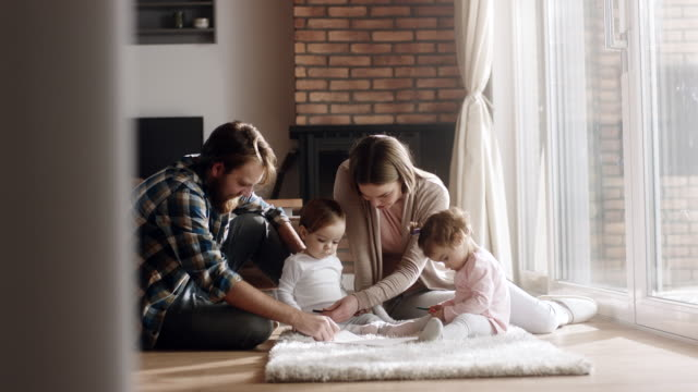 Young family with two baby girls spending time together at home