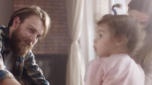 若い家族と家庭で一緒に時間を過ごす二人の赤ちゃん女の子 - 若い家族点の映像素材/bロール