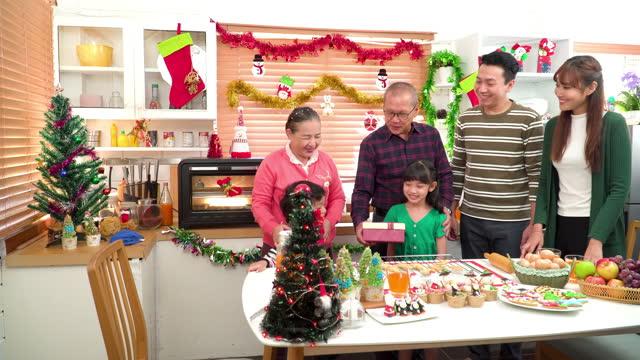 ํjunge familie mit zwei kindern wiedersehen zu großeltern, großvater, großmutter bereiten weihnachtsdessert, lebkuchenkeks, weihnachtsbaum cupcake zu herzlichem empfang sohn in der küche für weihnachtsfeier , südostasiatische mehrgenerationenfamili - 35 39 years stock-videos und b-roll-filmmaterial