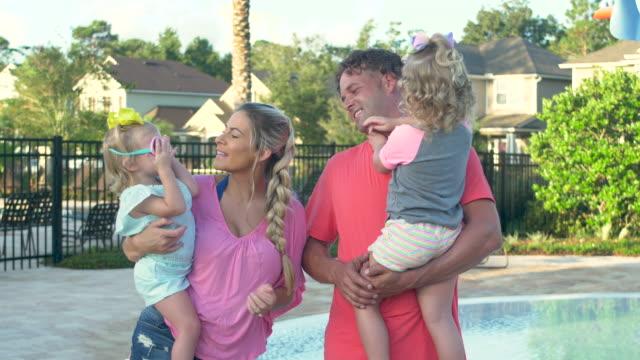 junge familie mit zwei mädchen im gemeinschaftspool - 30 34 years stock-videos und b-roll-filmmaterial