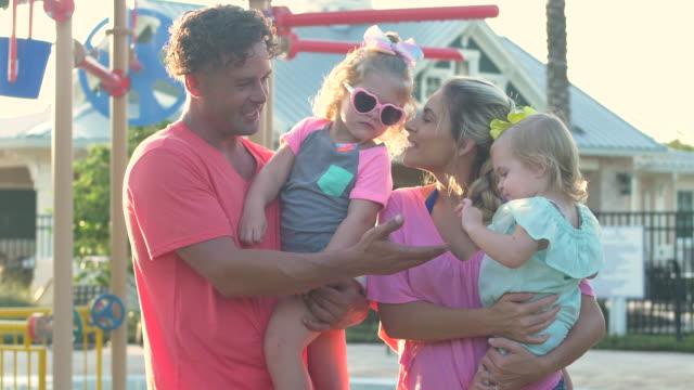 vídeos de stock, filmes e b-roll de família jovem com duas meninas na piscina comunitária - 4 5 years