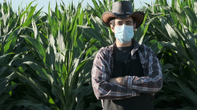 young farm worker posing looking at the camera wearing a protective face mask - lavoratore agricolo video stock e b–roll