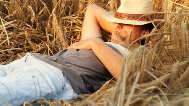 stockvideo's en b-roll-footage met hd: young farmer lying in wheat - cowboyhoed