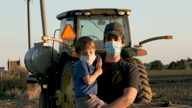 young farmer posing with his son, both wearing protective face masks - rural scene stock videos & royalty-free footage