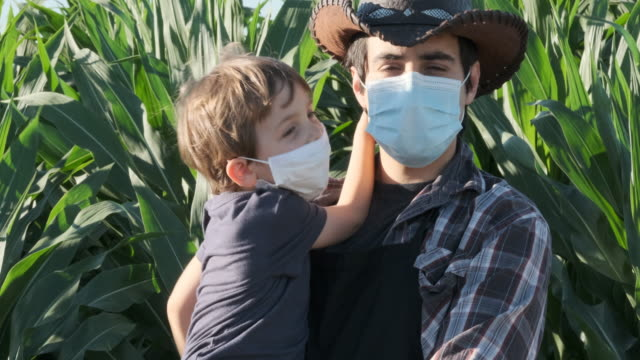 young farmer posing with his son, both wearing protective face masks - cowboy hat stock videos & royalty-free footage