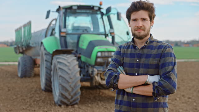 young farmer standing with arms crossed on field - landscaped stock videos & royalty-free footage