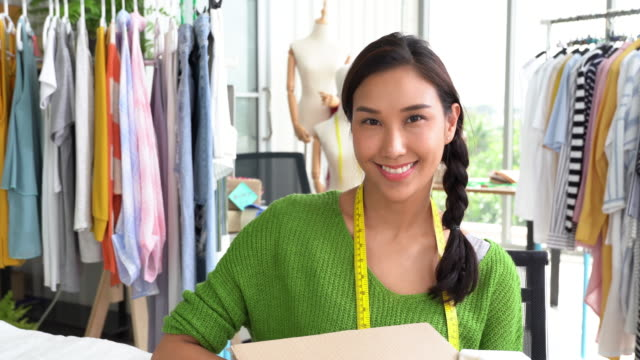 young fashion designer smiling at camera - fashion designer stock videos & royalty-free footage