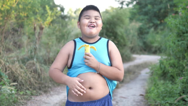 young fat boy peeling the skin from a banana - buccia video stock e b–roll
