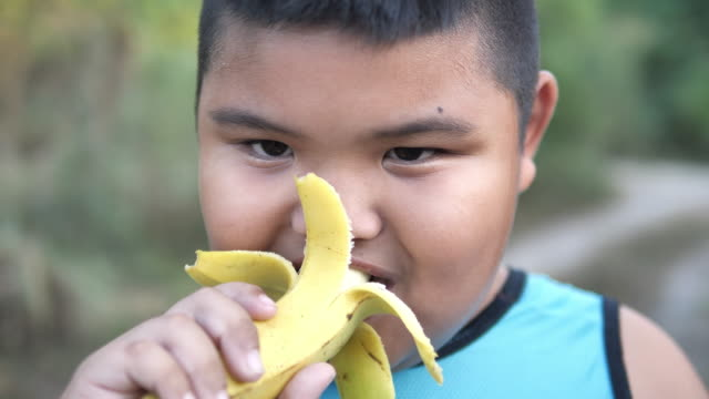 young fat boy peeling the skin from a banana - peel stock videos & royalty-free footage