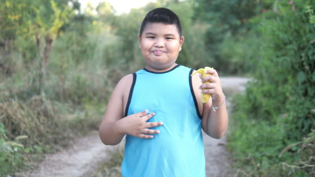 young fat boy peeling the skin from a banana - peel plant part stock videos & royalty-free footage
