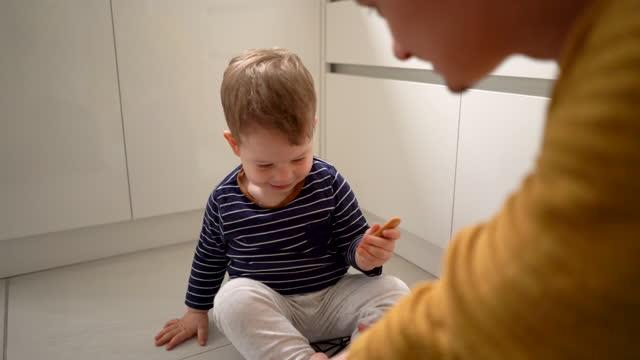 vídeos y material grabado en eventos de stock de padre joven e hijo pequeño jugando en el piso de la cocina en casa - genderblend