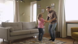 Young Father and Her Daughter Playing in Living Room. Funny Happy Family Father and Daughter are Dancing hold hands and jump at Home. Love Lifestyle Home. Slow Motion.