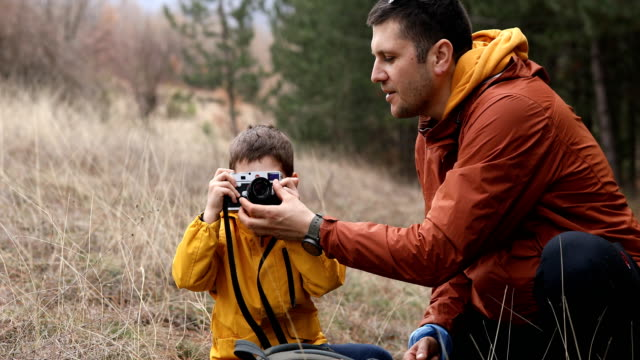 young father and little son with camera in nature - fotografo video stock e b–roll