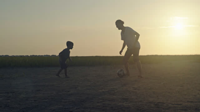 Young father and son play soccer in coastal marshland at sunrise.