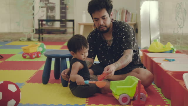 Young father and son playing on floor in living room.