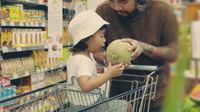 スーパーマーケットで買い物をする若い父と息子 - 生鮮食品コーナー点の映像素材/bロール