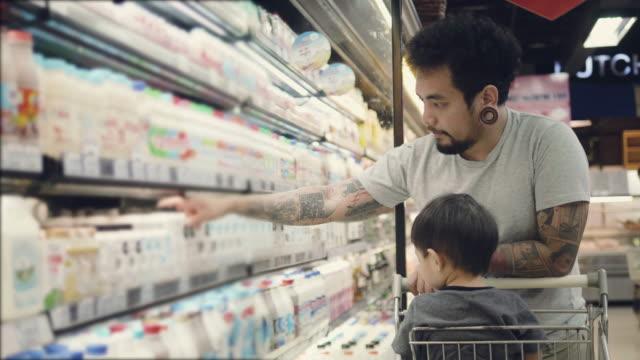 junger vater und sohn in einem supermarkt einkaufen - handwagen stock-videos und b-roll-filmmaterial