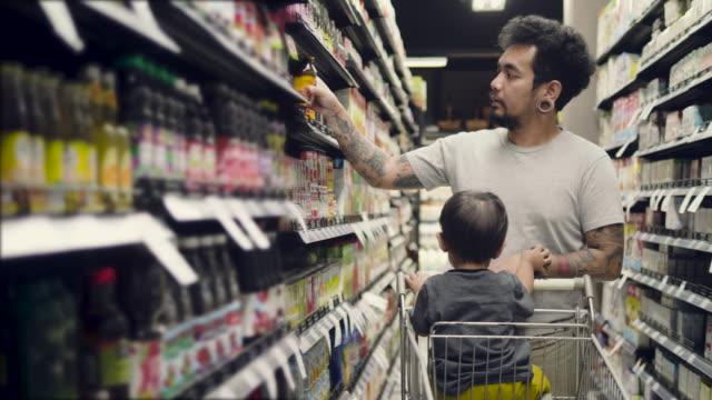 junger vater und sohn in einem supermarkt einkaufen - supermarkt stock-videos und b-roll-filmmaterial