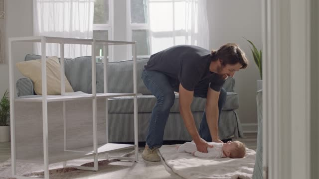 stockvideo's en b-roll-footage met young father assembles flat pack furniture and picks up baby in sunny home living room. - doe het zelven