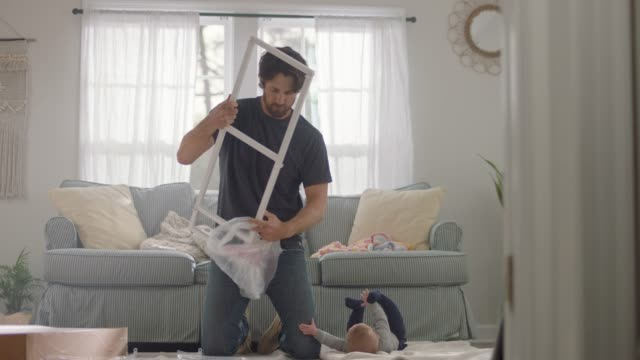 young father assembles flat pack furniture in home living room as baby reaches for him. - bricolage video stock e b–roll