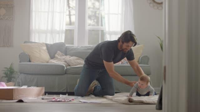 vídeos y material grabado en eventos de stock de young father assembles flat pack furniture while cute baby rolls around on blanket. - reforma