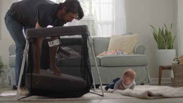 young father assembles pack and play while cute baby rolls around on blanket in home living room. - building activity stock videos & royalty-free footage
