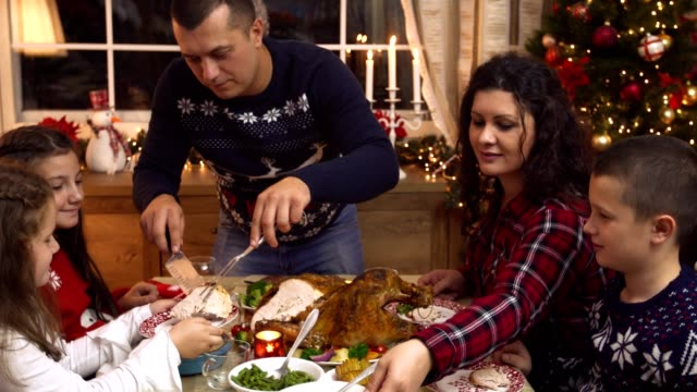 young father carving stuffed roasted turkey for christmas dinner - sharing stock videos & royalty-free footage