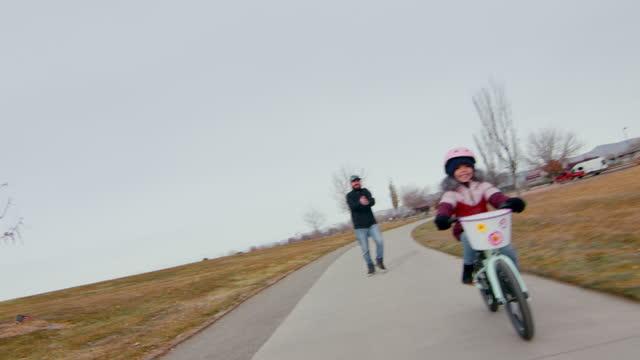 vídeos y material grabado en eventos de stock de joven padre aplaude y saluda a su hija de cuatro años mientras monta su nueva bicicleta sin sus ruedas de entrenamiento - 4 5 años