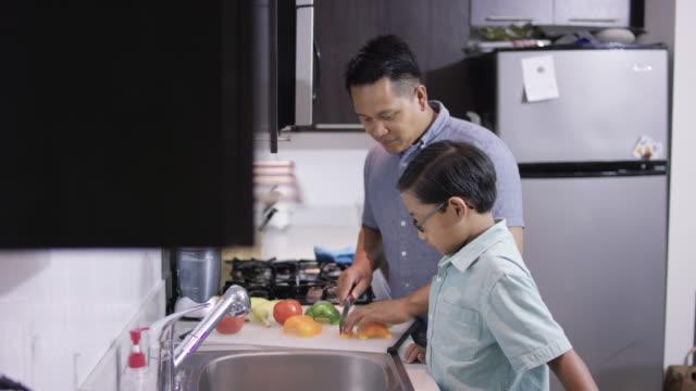 junger vater mit sohn in der küche kochen - sohn stock-videos und b-roll-filmmaterial