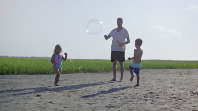 Young father, daughter, son and puppy play with bubbles in coastal marsh.