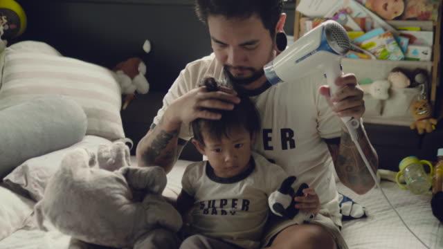 vídeos de stock, filmes e b-roll de jovem pai vestir menino - imitação