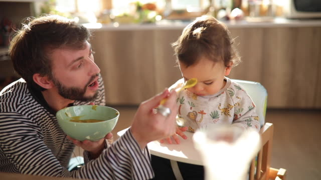 young father feeding his little son at home - feeding stock videos & royalty-free footage