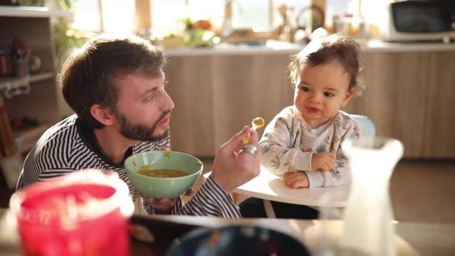 vídeos y material grabado en eventos de stock de joven padre alimentando a su pequeño hijo en casa - alimentar