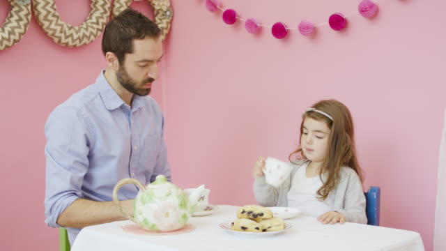 Young father having a tea party with his adorable daughter