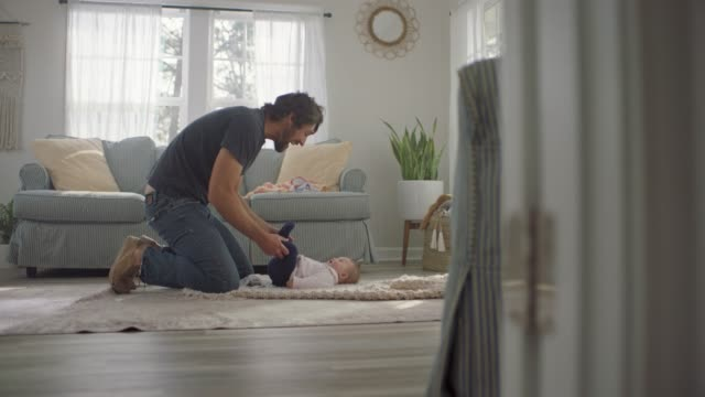 vídeos de stock e filmes b-roll de slo mo. young father helps his infant daughter learn to kick her legs as she looks up at him lovingly on living room floor. - aconchegante