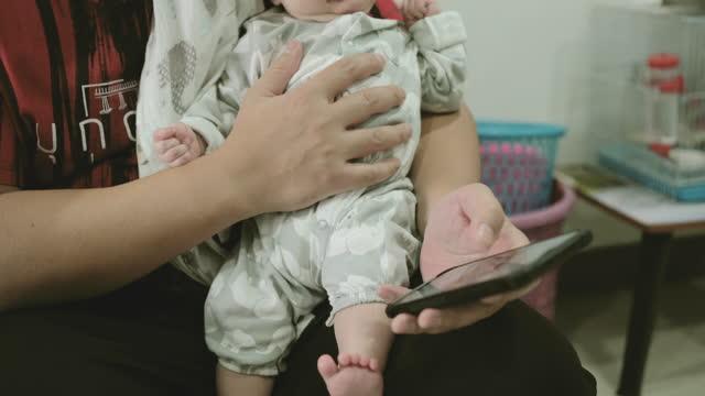 stockvideo's en b-roll-footage met jonge vader die baby houdt en een mobiel speelt. - genderblend