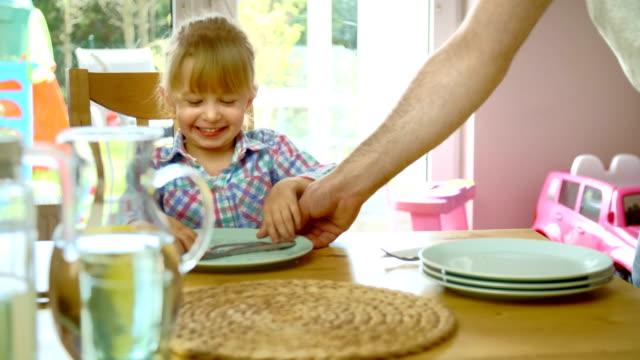 Junger Vater setzt den Tisch für seine Kinder