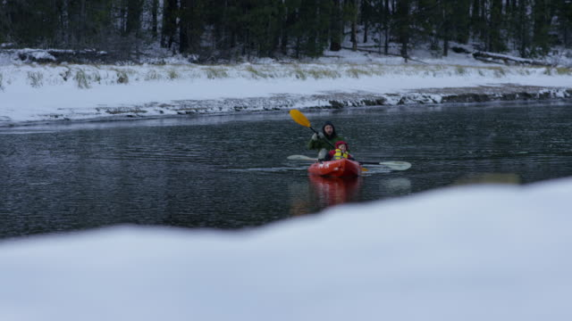 junger vater mit seinem sohn kajak fahren im winter - ruderboot stock-videos und b-roll-filmmaterial