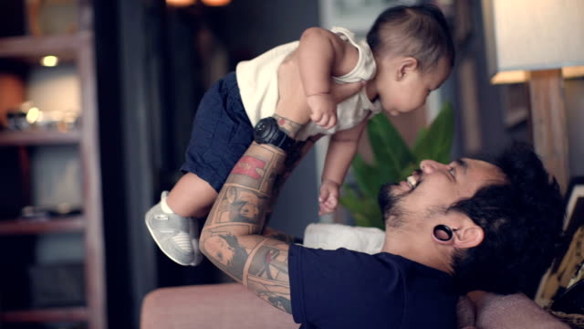 a young father lying on sofa - tattoo stock videos & royalty-free footage
