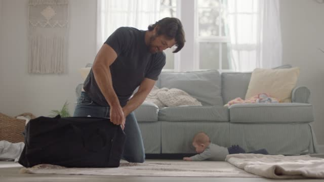 young father packs up portable crib and helps baby back on blanket as it tries to roll away. - multitasking bildbanksvideor och videomaterial från bakom kulisserna