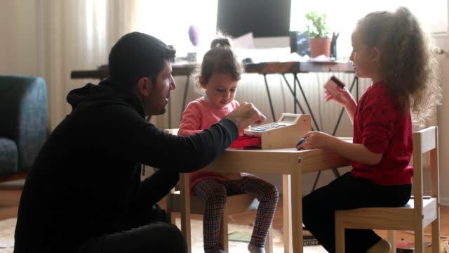 小さな子供たちと遊ぶ若い父親とおもちゃ - 社会福祉点の映像素材/bロール