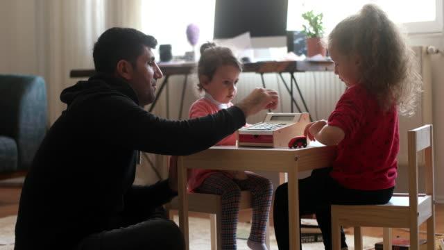 vídeos de stock, filmes e b-roll de jovem pai brincando com e brinquedos com crianças pequenas - irmão
