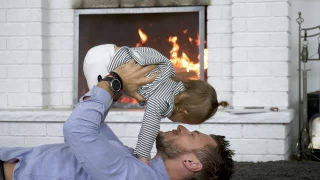 vídeos de stock e filmes b-roll de young father playing with his daughter at home by the fire - lareira